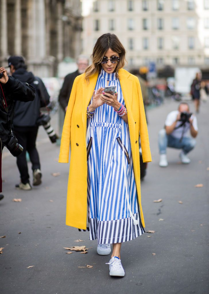 Ulica style woman in striped dress yellow coat and sneakers