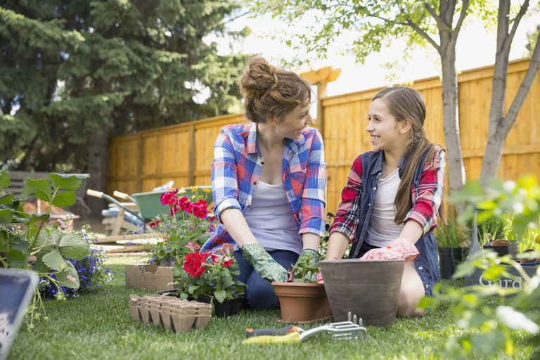 א picture of a mother and daughter planting flowers