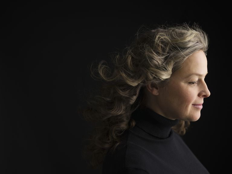 Profil portrait serene woman with curly gray hair looking down against black background