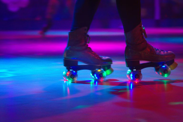 Ниско Section Of Person Roller Skating On Floor In Illuminated Rink