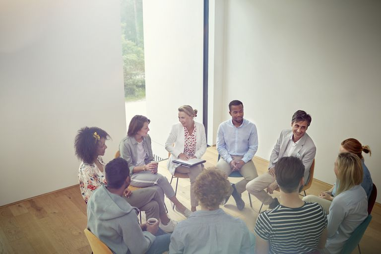 Ljudje talking in a circle in group therapy session