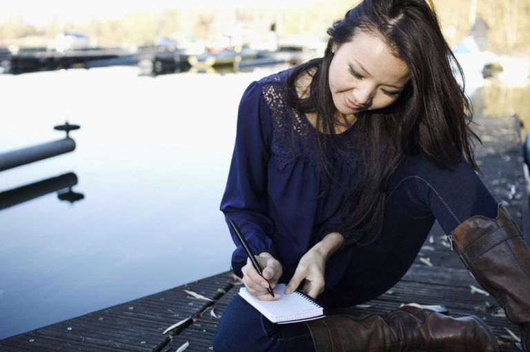 A woman journaling on a deck.