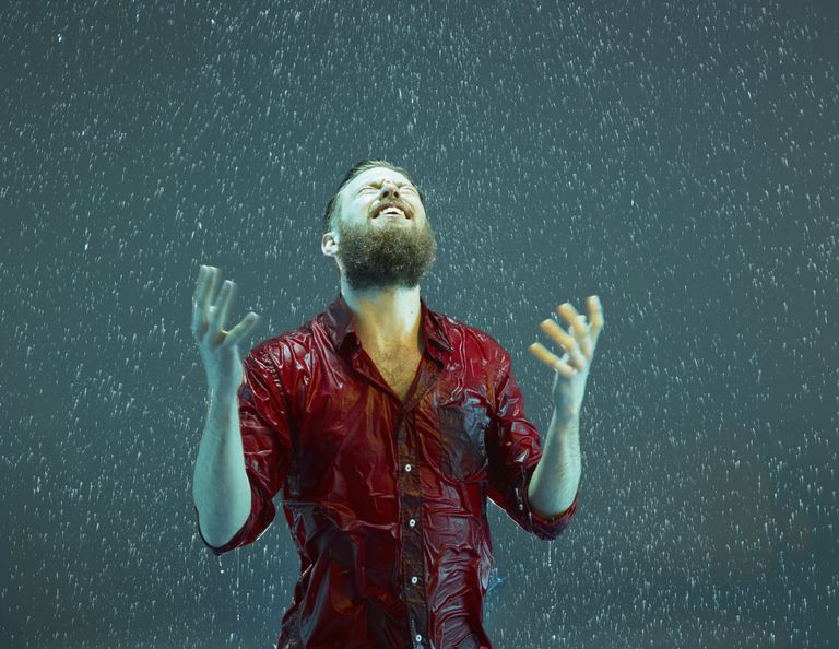 A man laughing in the rain.