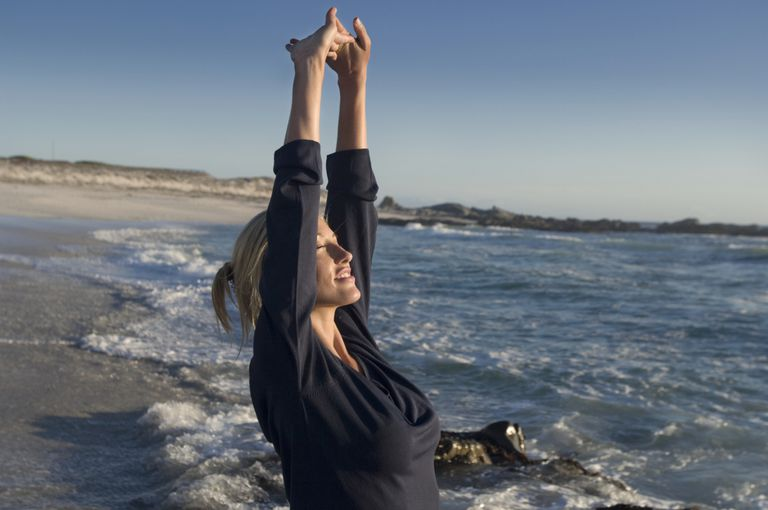 A woman breathing and stretching at the ocean.