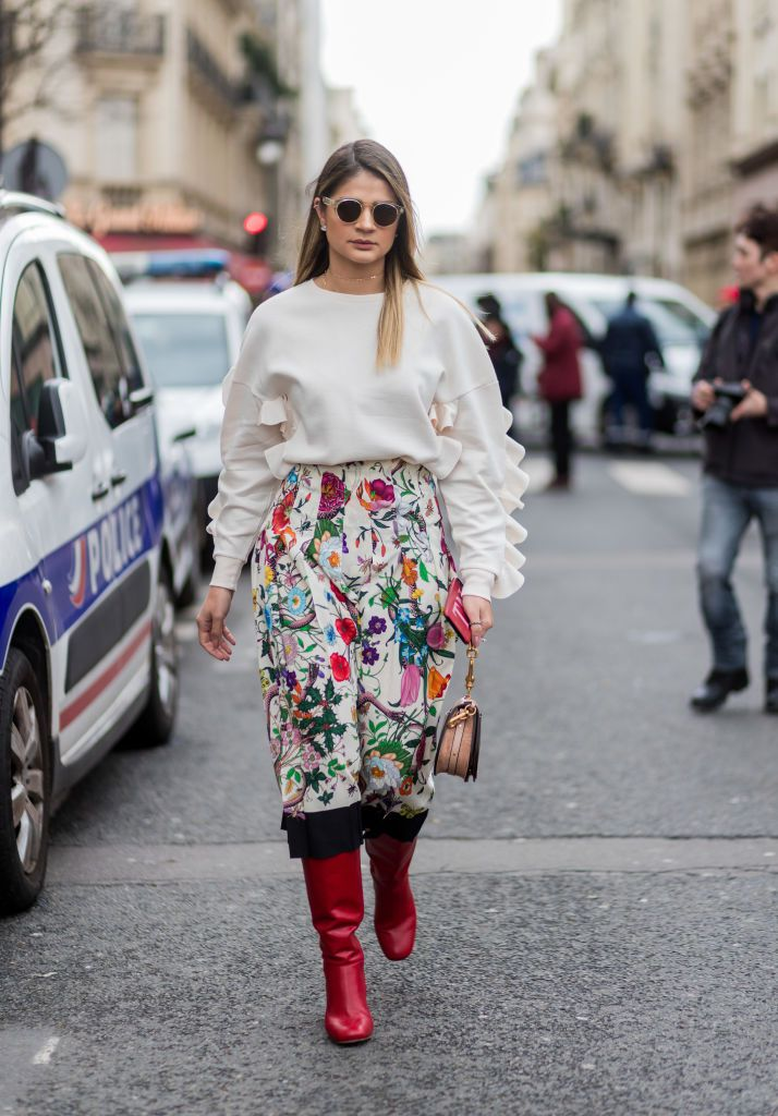 Gata style in sweater and floral print skirt and boots