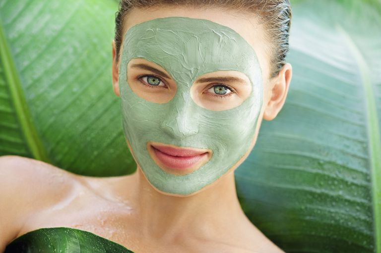 Nő with face green mud mask among big leaves