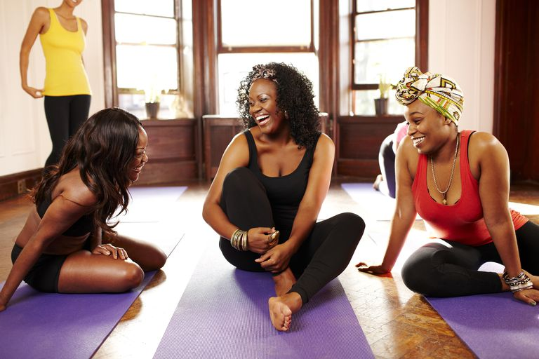 kvinnor friends laughing in yoga class