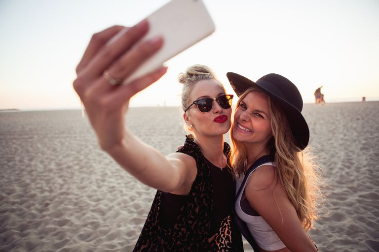 महिलाओं taking selfies on the beach.