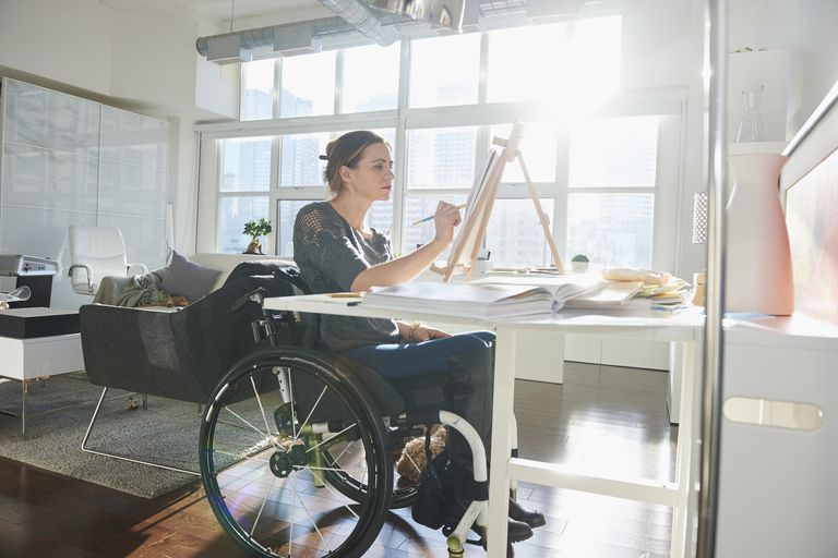 Кавкаски woman in wheelchair painting on easel