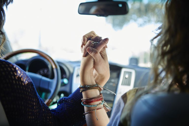 Två young women holding hands in car