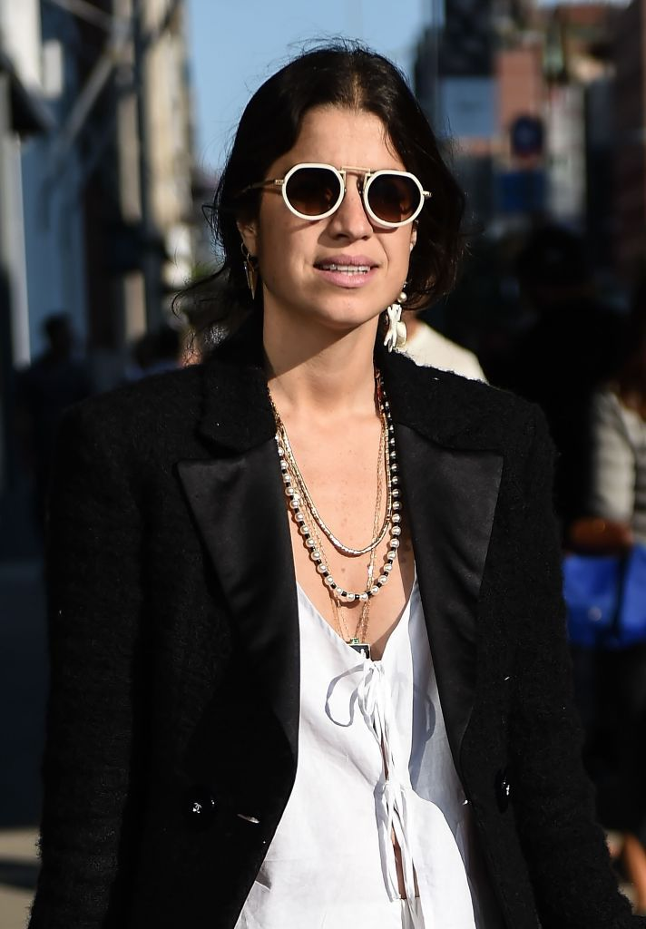 Femeie wearing sunglasses and multiple necklaces