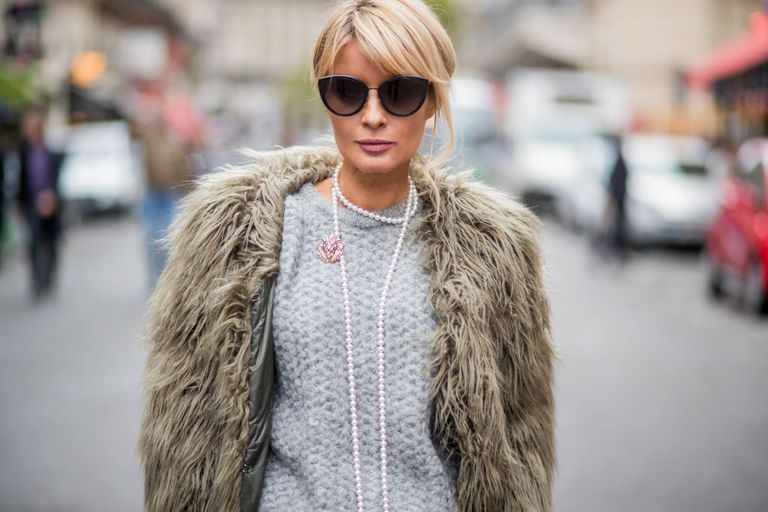 Stradă style fashion photo woman in faux fur and pearl necklaces