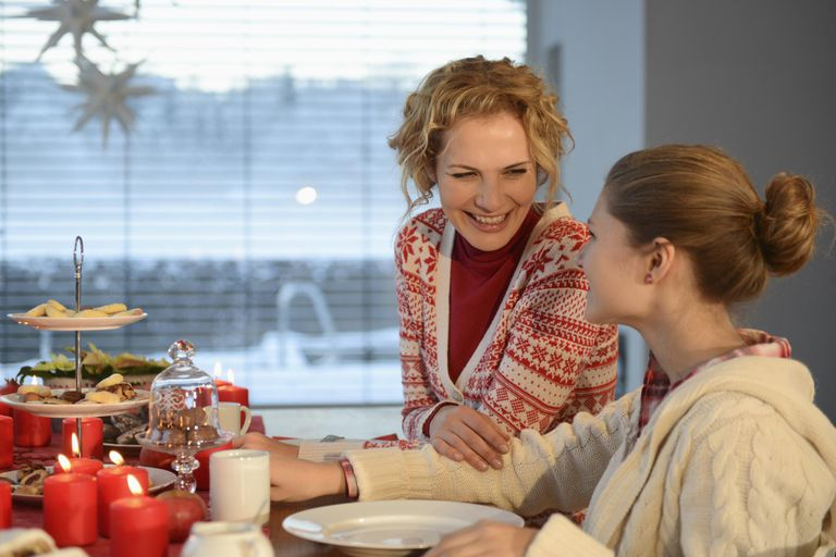 srednji adult woman smiling at daughter at dinner table at Christmas time