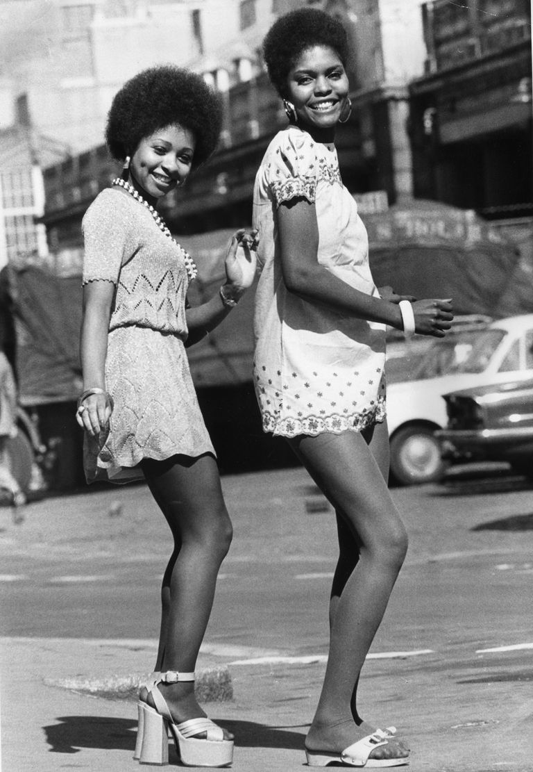 שתיים models, photographed in 1973, wearing mini dresses, one with platform sandals, the other in flat exercise sandals.