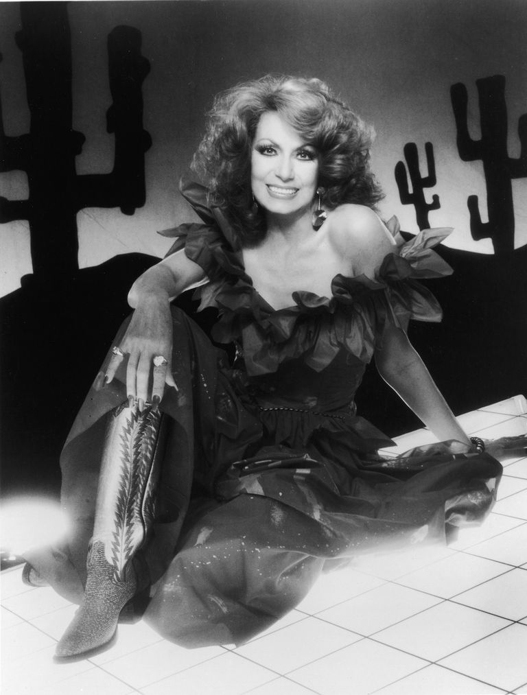 שָׁחוֹר and white photo of country singer Dottie West, wearing fancy dress and cowboy boots.