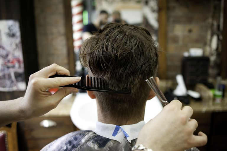 Bak view of young man in barbershop having haircut