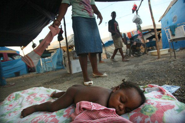 An Haitian infant is fanned by another Haitian child while sleeping under a tent in a tent city.