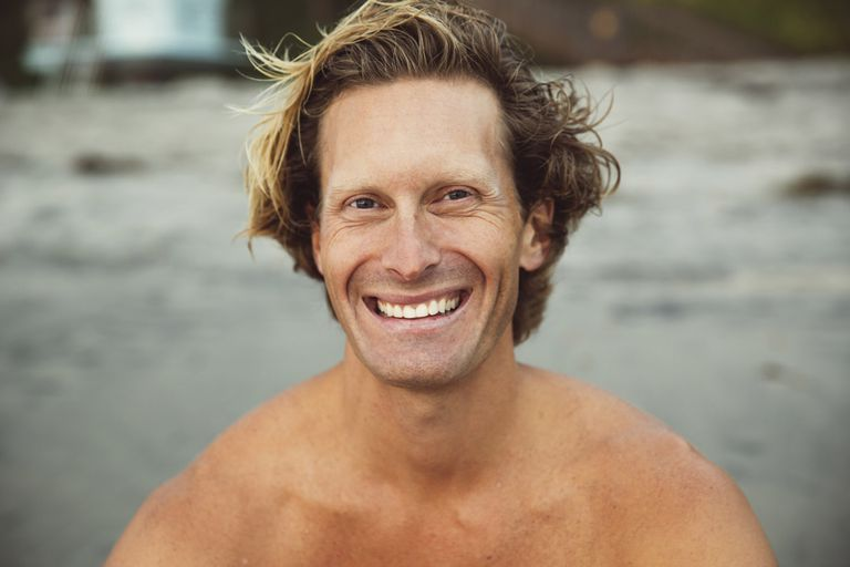 shirtless man smiling on the beach