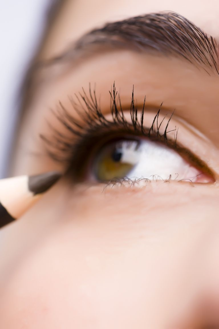 Extrem close up of a woman eye with make up pencil