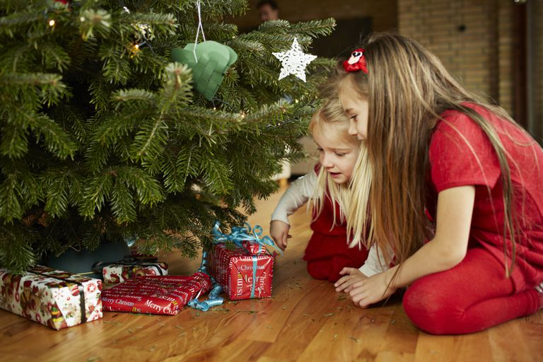 Söt girls grabbing presents under christmas tree
