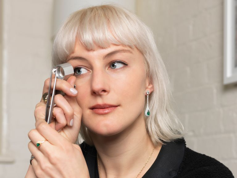 en woman using a jeweler's loupe