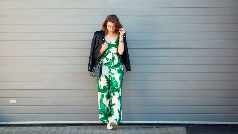 Ženska wearing tropical print jumpsuit and black leather motorcycle jacket