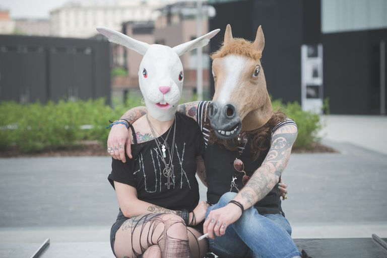 A couple wearing animal heads sits together.