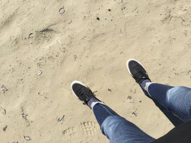 Особа in jeans standing on a beach