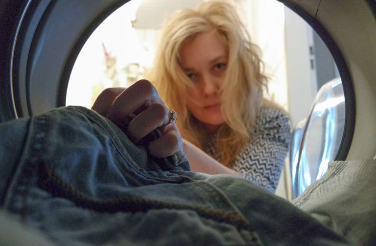 Жена putting jeans in washing machine