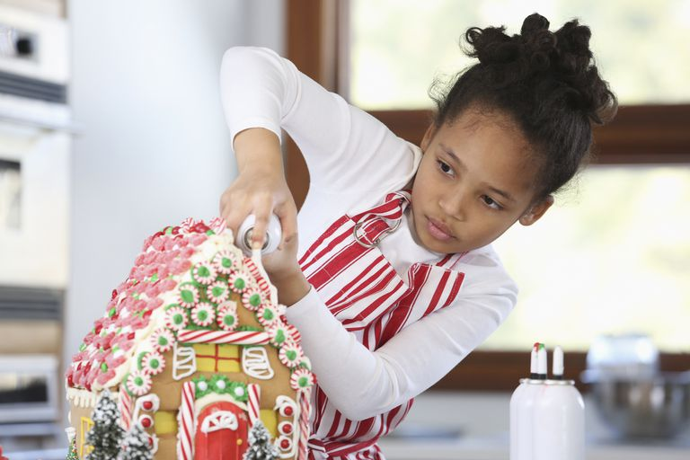 Svart girl decorating gingerbread house