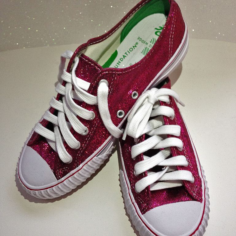 Паир of red, glittered sneakers with white shoe laces and trim.