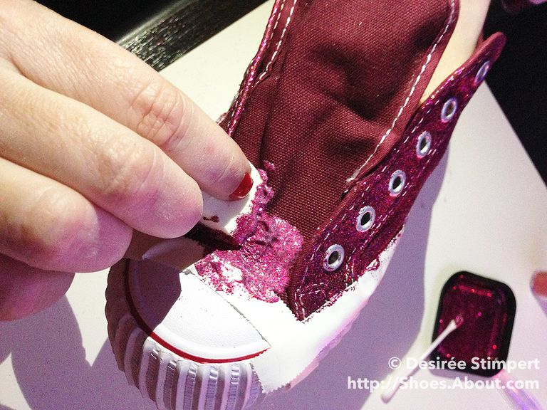 Слика of glitter and glue mix being sponged onto the tongue of a red sneaker.