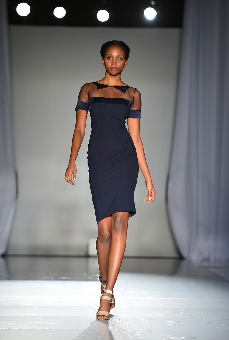 Model walking down runway in navy dress and neutral sandals.
