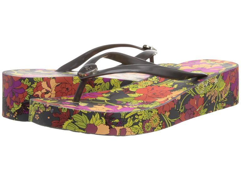 Kvinnor's flip flops with black floral soles and wedge heels.