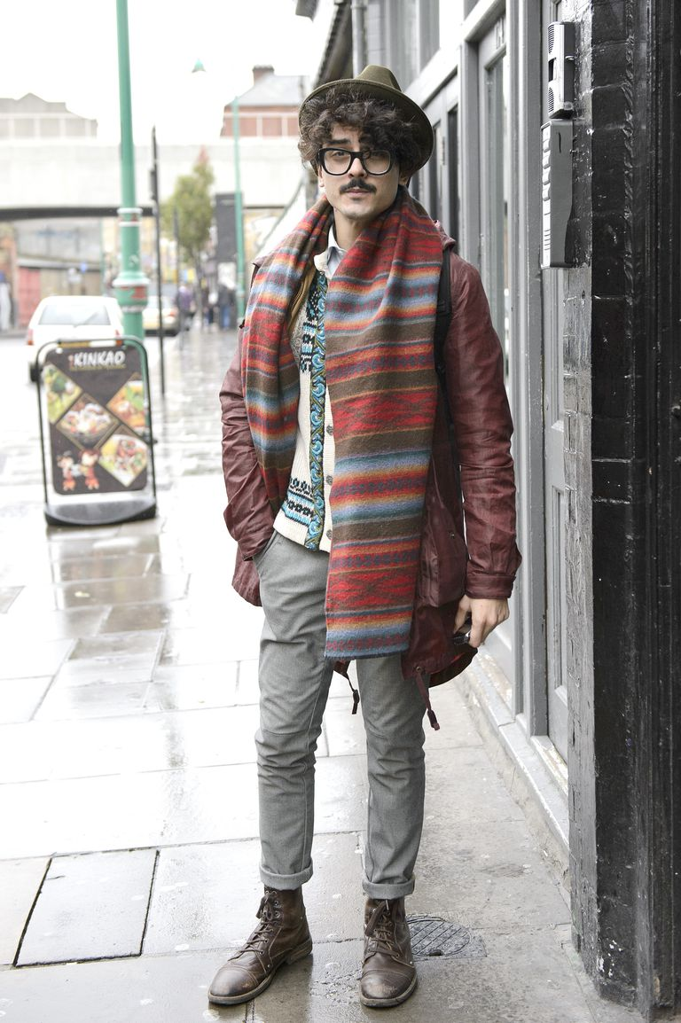 Fotograf Raul poses wearing a vintage hat, jumper, scarf and trousers with a Gap Jacket, Dolce Gabbana Glasses, and Farrah boots.
