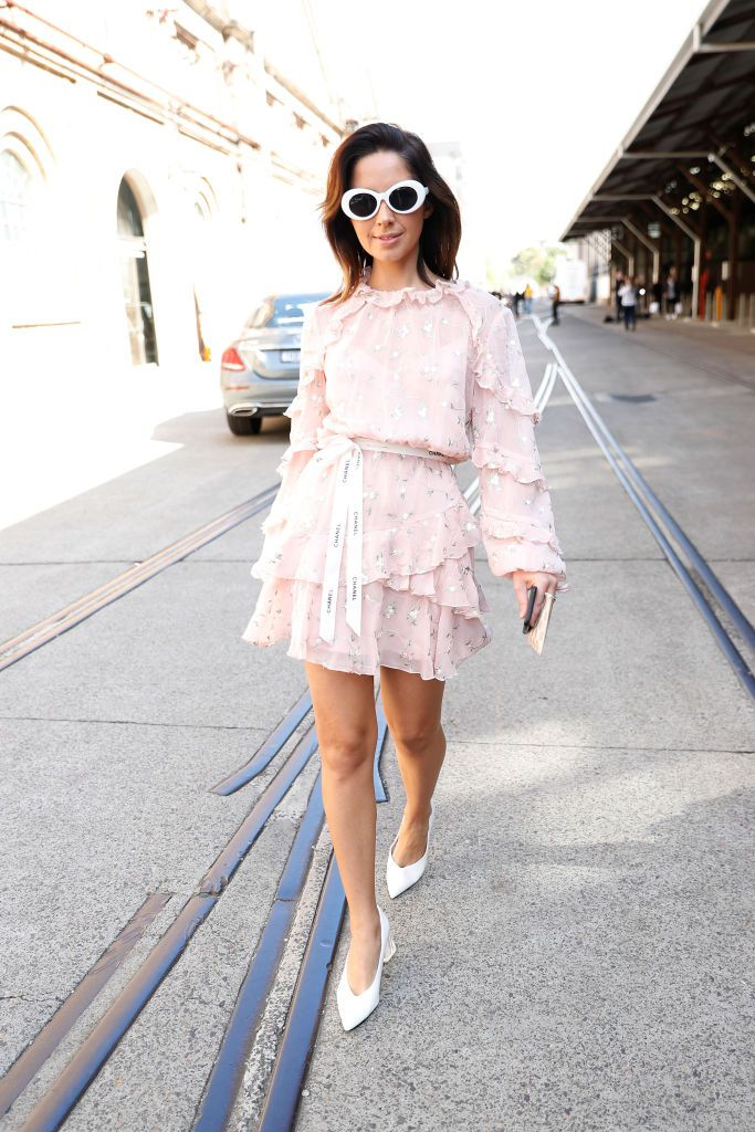 หญิง wearing ruffled dress and white sunglasses and white shoes