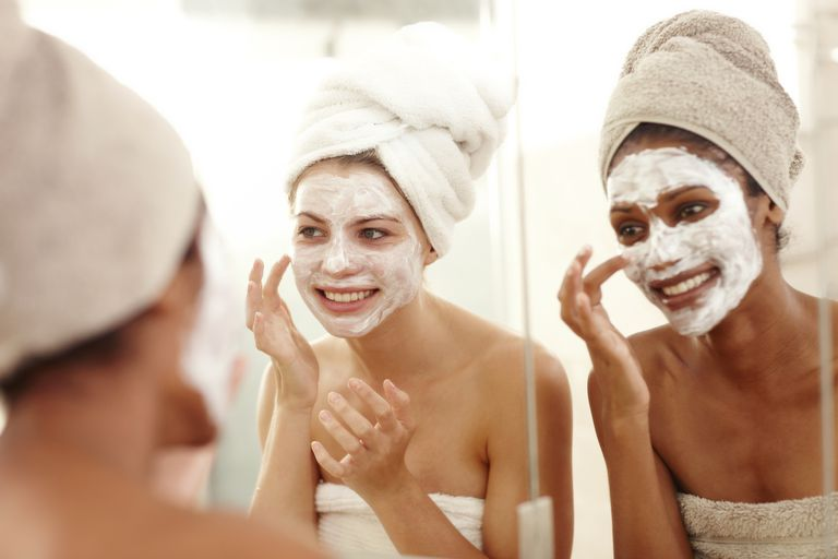 Жене applying a face mask