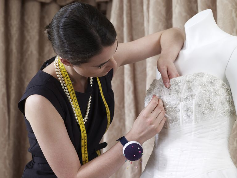 นักออกแบบ making adjustments to wedding gown