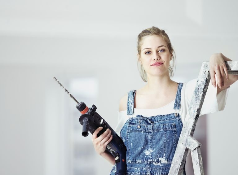 Žena in overalls with drill