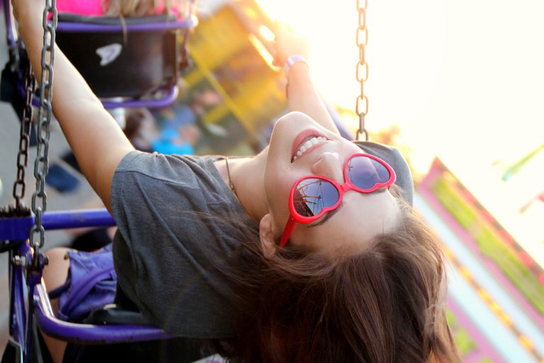Tineri girl sitting on swing wearing heart shaped sunglasses