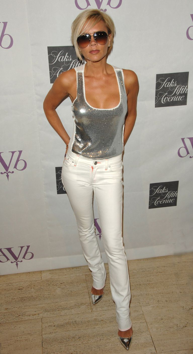 Victoria Beckham, dressed in silver tank top; silver pointy-toed pumps; and white jeans.