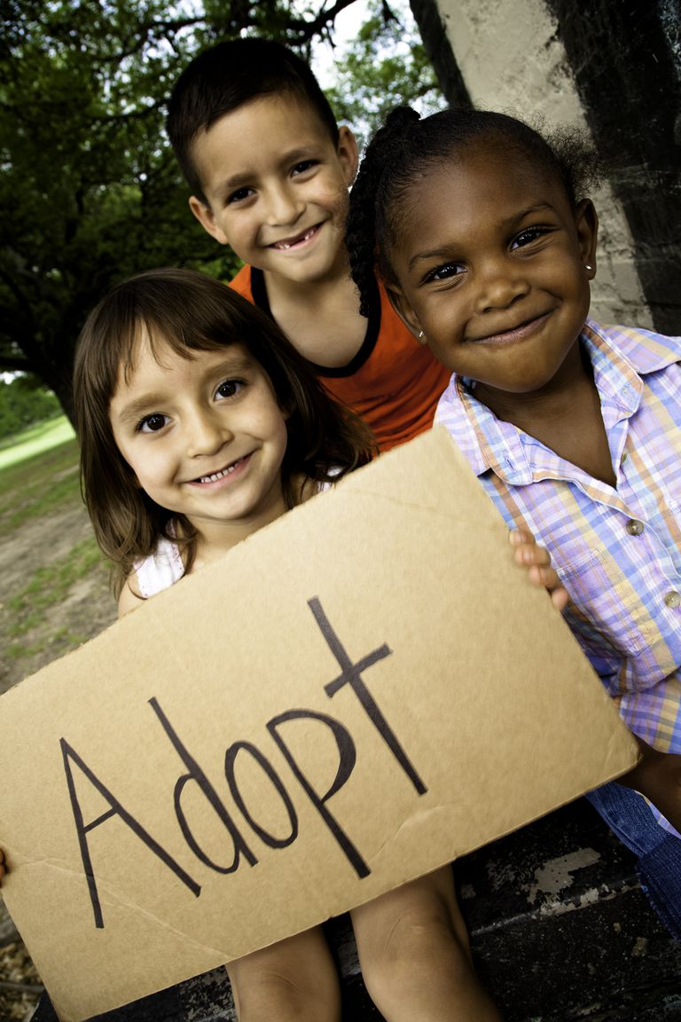 קְבוּצָה of Little Children Holding Sign Reading ADOPT