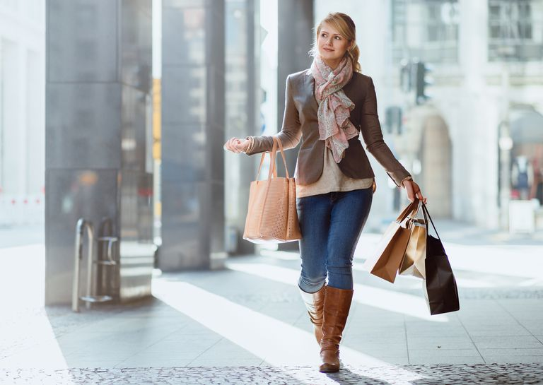 petit woman walking with shopping bags
