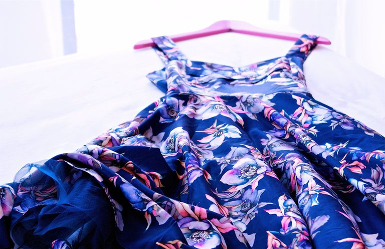 Kék dress with purple flowers laying on a bed