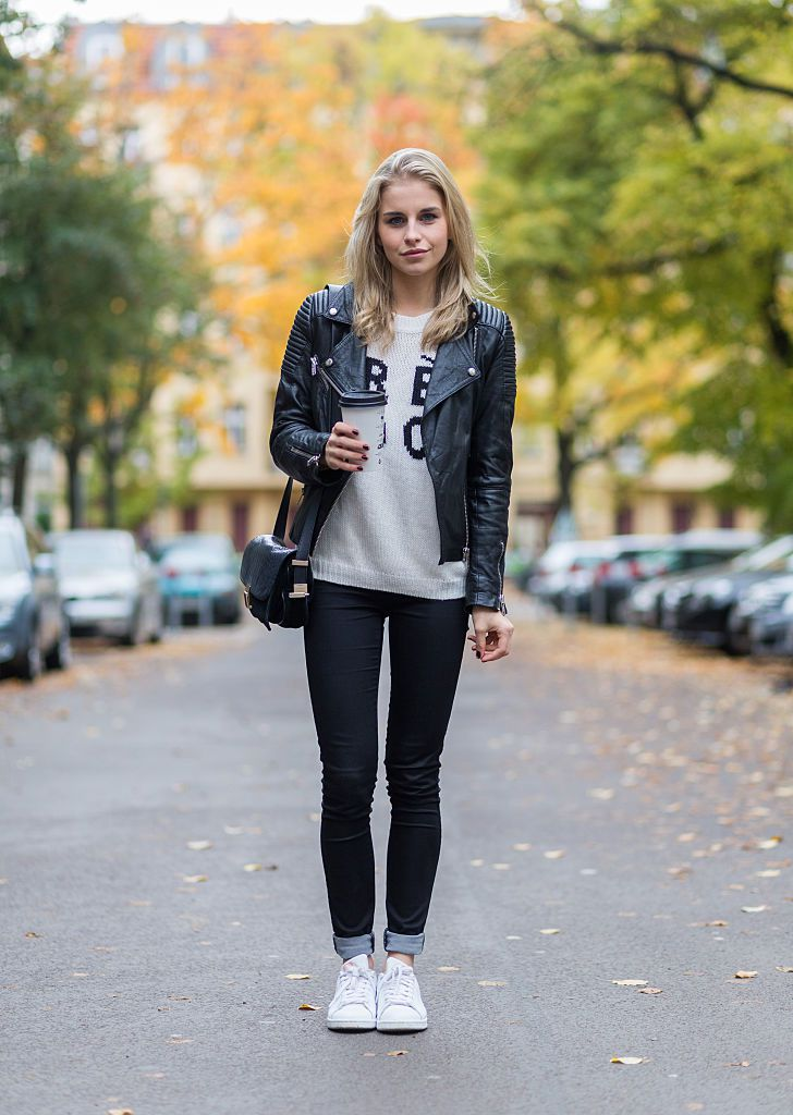 רְחוֹב style photo of woman wearing black jeans and Adidas sneakers